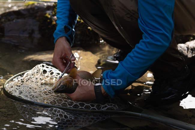 Sección baja de pescador quitar gancho de pesca de peces con tijera - foto de stock