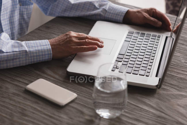 Close-up of senior man using laptop at home — Stock Photo