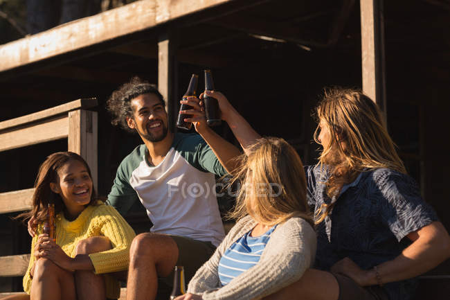 Happy group of friends toasting beer bottle on cabin — Stock Photo