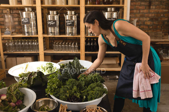 Beautiful female staff checking vegetable in supermarket — Stock Photo