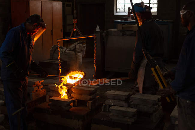 Workers pouring molten metal from flasks into moulds in foundry — Stock Photo