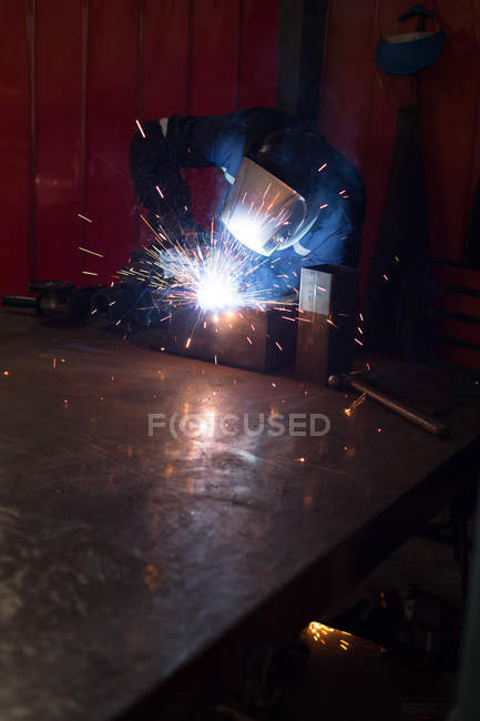 Robotic engineers using welding torch in warehouse — Stock Photo