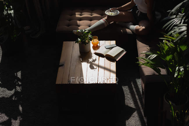 Mulher ter comida no sofá na sala de estar em casa — Fotografia de Stock