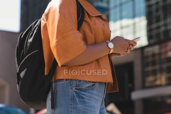 Milieu de la section de la femme utilisant le téléphone mobile en ville — Photo de stock
