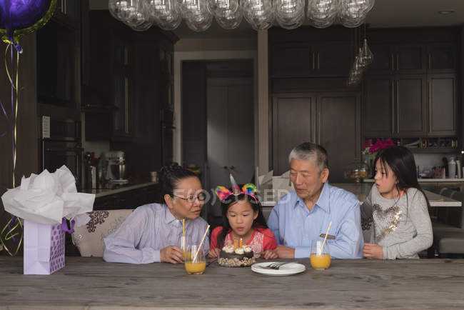 Grandparents celebrating their granddaughters birthday at home — Stock Photo