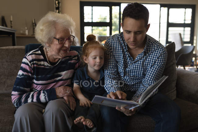 Multi generation family reading book on sofa in living room at home — Stock Photo