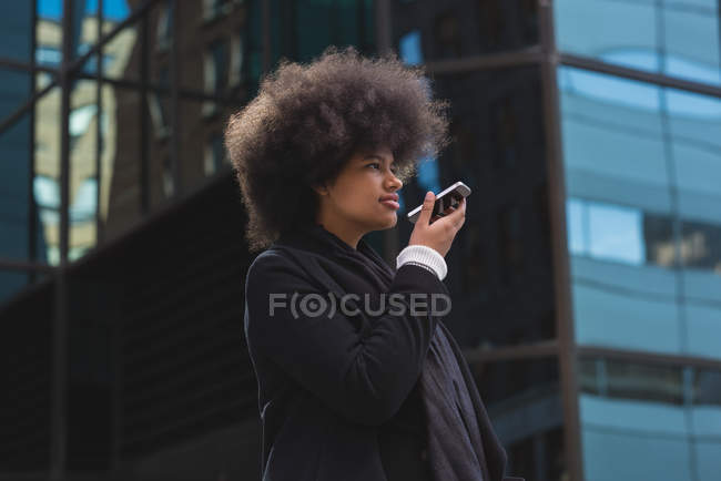 Young woman talking on mobile phone in city — стоковое фото