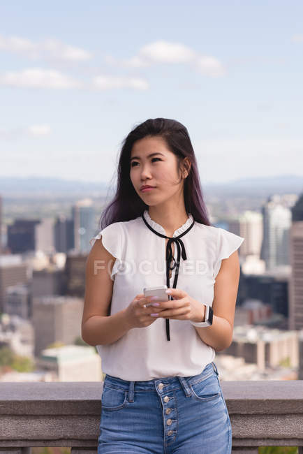 Thoughtful woman using mobile phone on a sunny day — Stock Photo