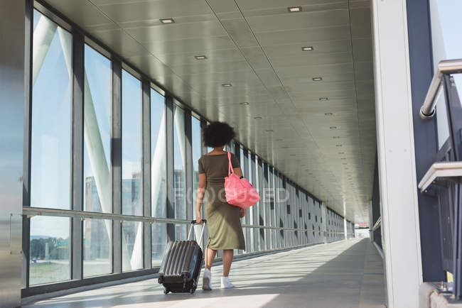 Rear view of woman with luggage bag walking at airport — Stock Photo