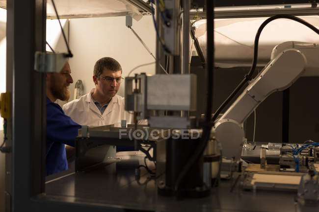 Attentive robotic engineers working in warehouse — Stock Photo