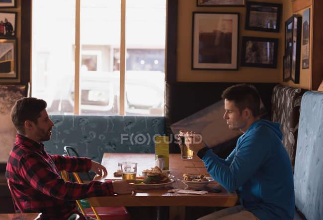 Freunde, die miteinander reden und dabei Getränke im pub — Stockfoto