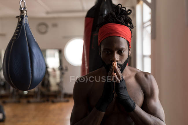 Young male boxer looking at camera in fitness studio — Stock Photo