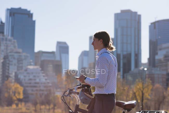 Людина, що використання мобільного телефону під час прогулянки з велосипеда в місті сонячний день — стокове фото
