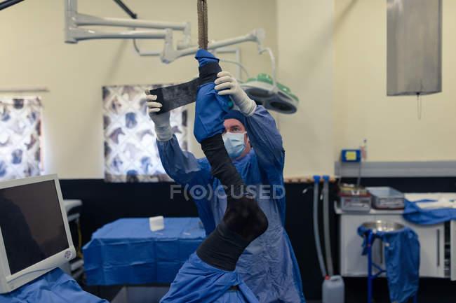 Хирург, применяя повязки лошади в театре операции в больнице — стоковое фото