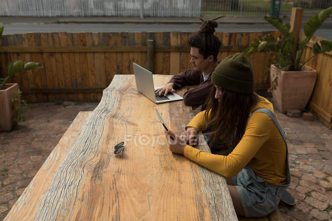 Young skateboarders using multimedia devices at outdoor cafe — Stock Photo