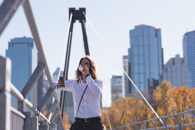 Человек, использующий мобильный телефон во время кофе на мосту в городе — стоковое фото