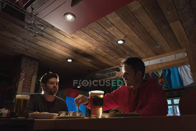 Young friends enjoying their drinks in pub — Stock Photo