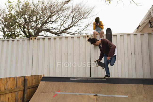 Junge weibliche Skateboarder Klick Foto während männliche Skater Skaten auf Skateboardrampe — Stockfoto
