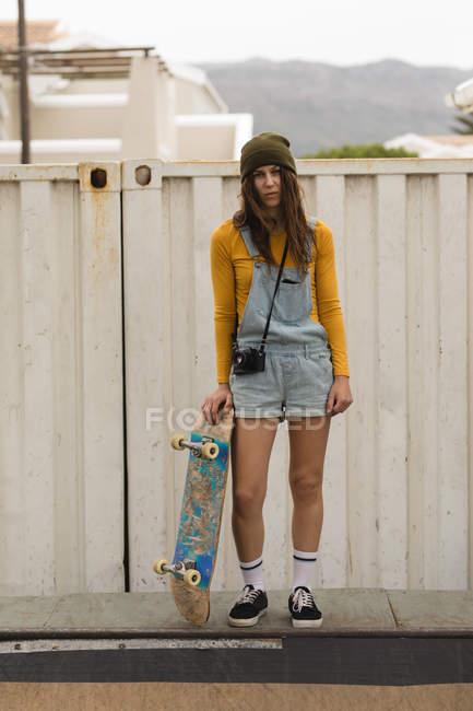 Schöne weibliche Skateboarder stehend mit Skateboard auf Skateboardrampe — Stockfoto