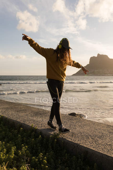 Young woman walking on wall near beach — стоковое фото