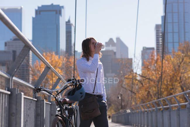 Мужчина пьет кофе, стоя с велосипедом на мосту в городе — стоковое фото
