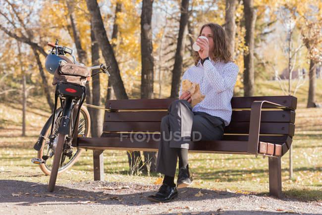 Молодой человек пьет кофе, сидя на скамейке в парке — стоковое фото