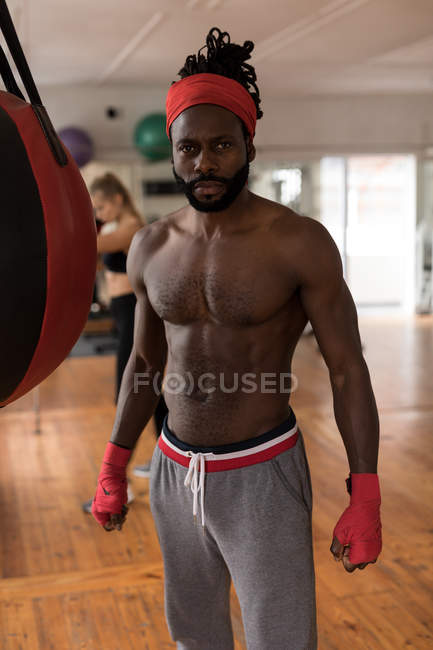 Portrait of shirtless male boxer standing in fitness studio — Stock Photo