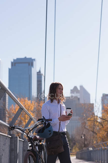 Hombre usando el teléfono móvil mientras toma café en el puente de la ciudad - foto de stock