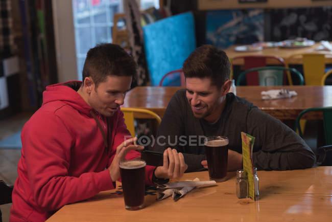 Друзья, обсуждения на мобильном телефоне за столом в пабе — стоковое фото