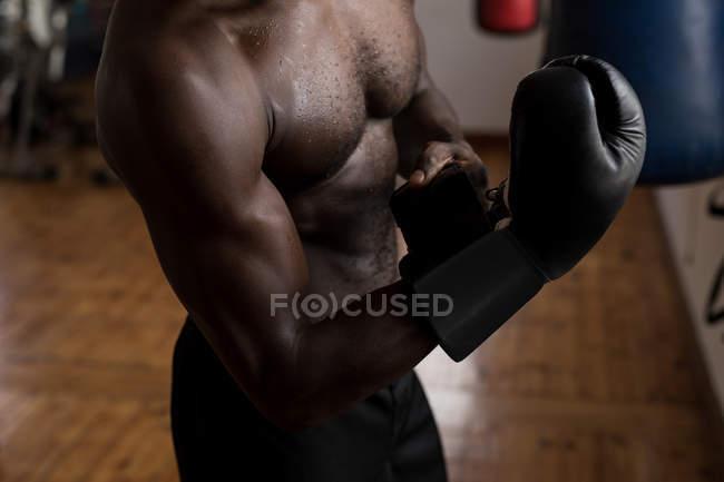 Partie médiane du boxeur masculin portant des gants de boxe dans un studio de fitness — Photo de stock