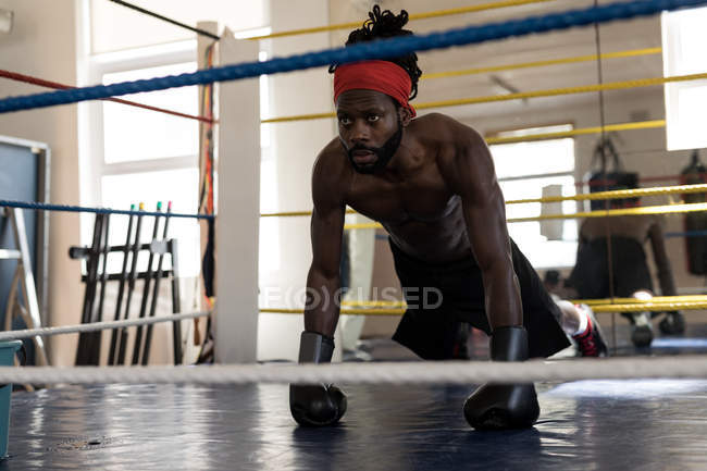 Male boxer doing push ups in boxing ring at fitness studio — Stock Photo