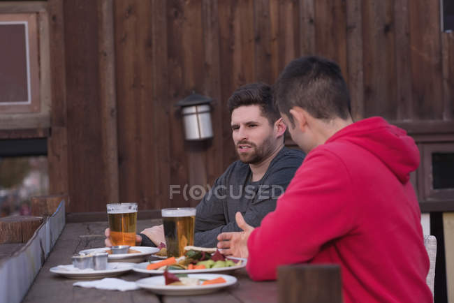 Friends talking with each other while having drinks at outdoor pub — Stock Photo