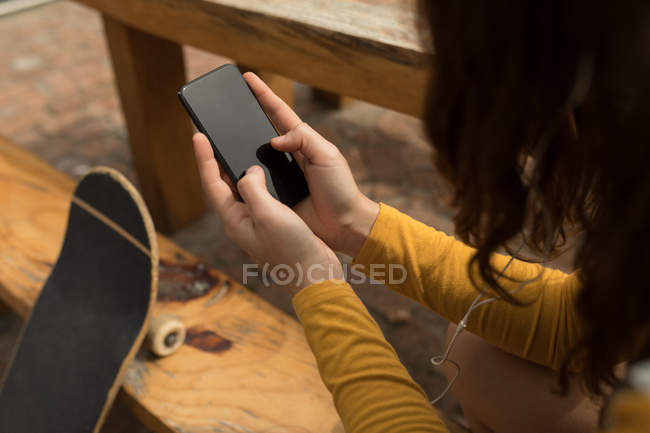Close-up of female skateboarder using mobile phone at outdoor cafe — Stock Photo