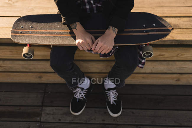 Low section of skateboarder sitting with skateboard on wooden bench — Stock Photo