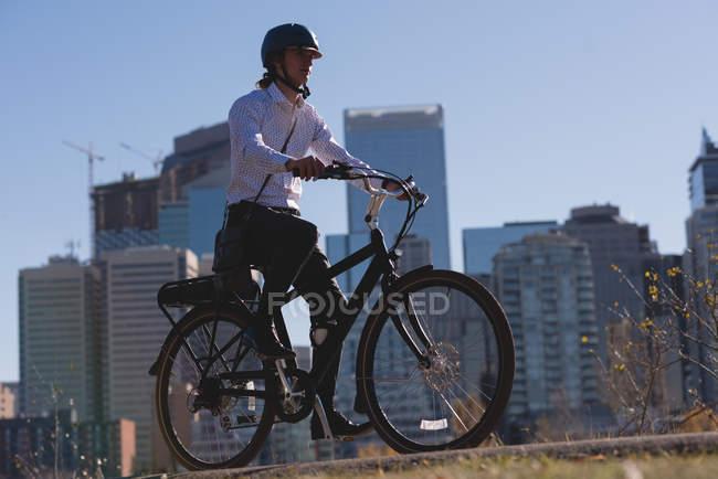 Молодой человек катается на велосипеде по дороге в городе — стоковое фото