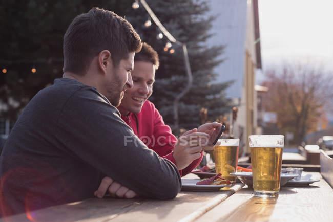 Amigos, discutindo no telefone celular enquanto bebendo no bar ao ar livre — Fotografia de Stock