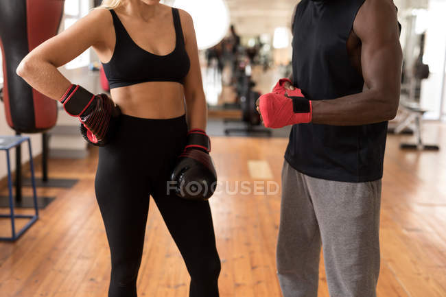 Средняя секция тренера мужского пола, помогающего женщине-боксеру в фитнес-студии — стоковое фото