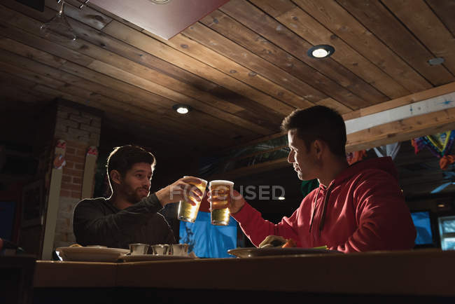 Young friends toasting beer glasses in pub — Stock Photo