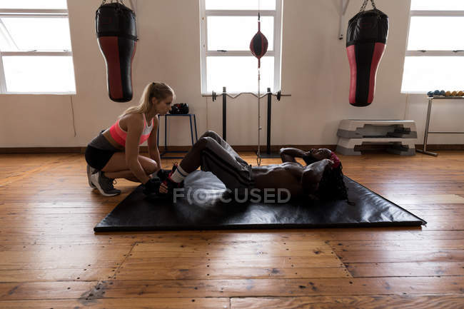 Female trainer assisting male boxer in doing crunches in fitness studio — стоковое фото