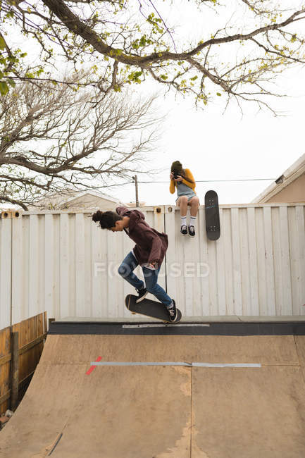 Young female skateboarder clicking photo while male skateboarder skating on skateboard ramp — Stock Photo