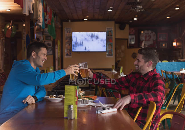 Happy friends toasting beer glasses in pub — Stock Photo