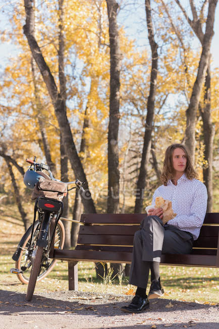 Thoughtful man relaxing on the bench in the park — Stock Photo