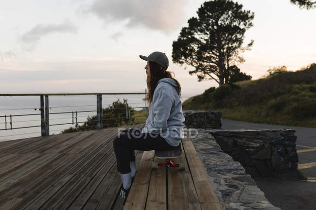 Side view of female skateboarder sitting on skateboard by railing at observation point — Stock Photo