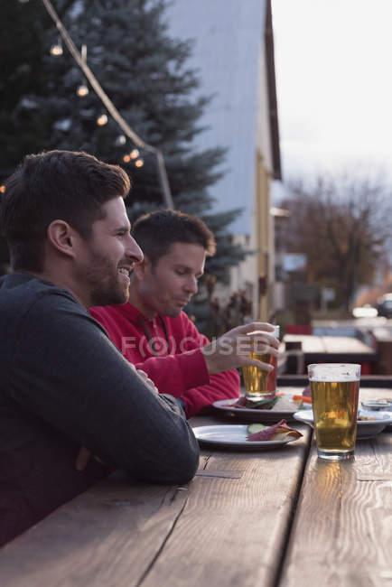 Young friends enjoying their drinks at outdoor pub — Stock Photo