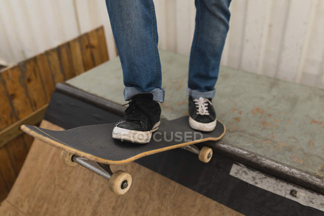 Niedrige Teil der Skateboarder stehend mit Skateboard auf Skateboardrampe am Skateboard Hof — Stockfoto