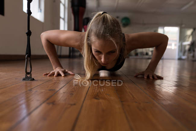 Young female boxer doing push ups in fitness studio — Stock Photo