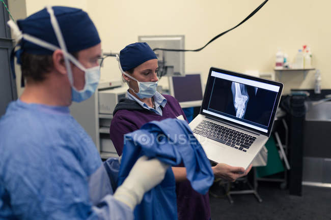 Female nurse showing x-ray report to male surgeon on laptop in hospital — Stock Photo