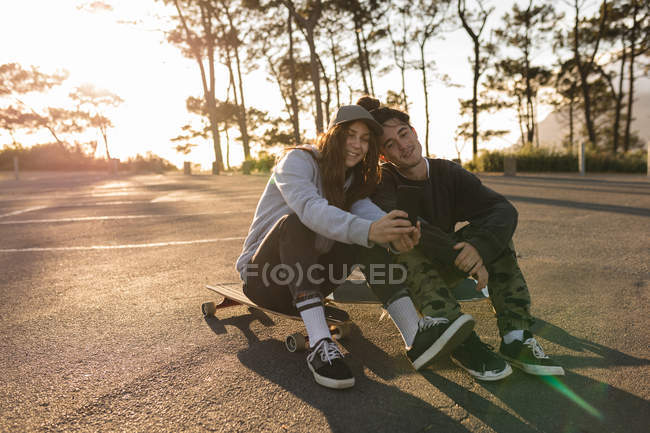 Happy couple skateboarder prendre selfie sur mobile à la route de campagne — Photo de stock