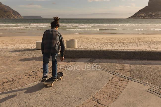 Rear view of man skateboarding at beach — стоковое фото