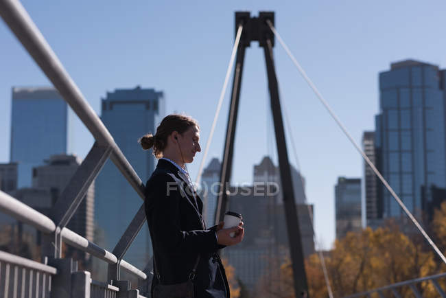 Thoughtful man holding coffee on the bridge in the city — Stock Photo